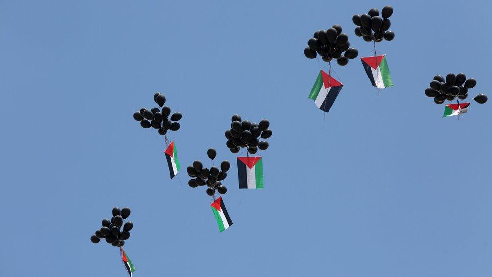 Globos negros se elevan con banderas palestinas