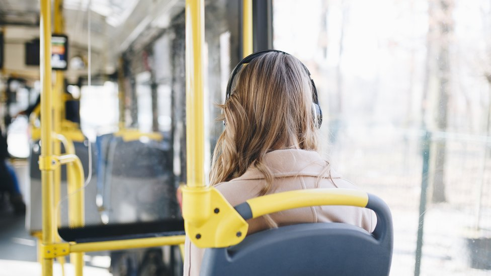 Woman listens to headphones on the bus