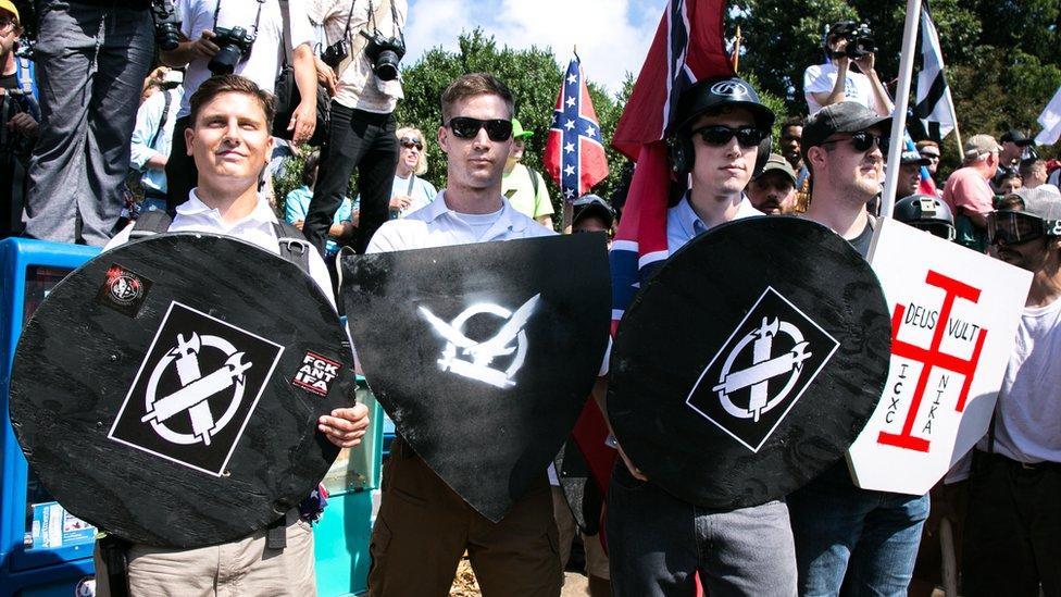 Nacionalistas blancos sujetan escudos con símbolos en ellos (Charlottesville, Virginia, 2017)