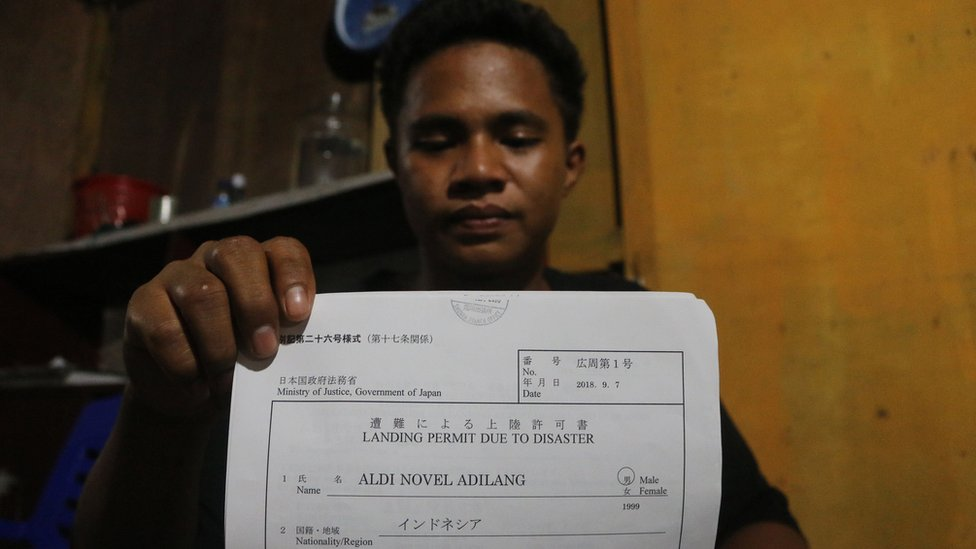 """Mr Adilang holds a document showing he was allowed to land in Japan """"due to disaster"""""""