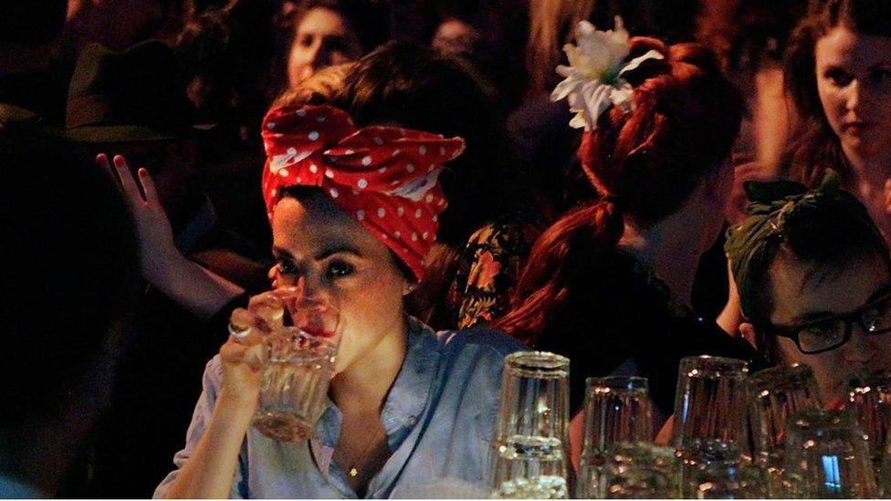 Una mujer toma agua en un bar.