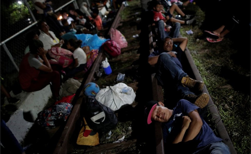 Honduran migrants rest on the bridge that links Mexico and Guatemala, in Ciudad Hidalgo, Mexico