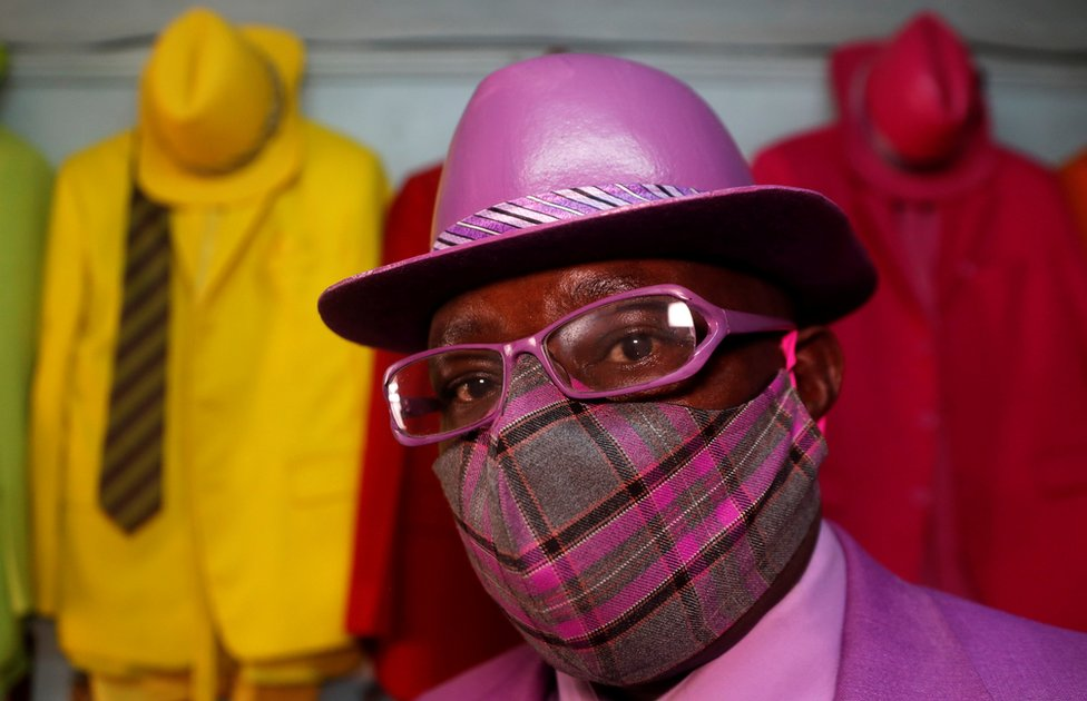 Kenyan fashionista James Maina Mwangi, dressed all in purple, stands beside green, yellow and red suits.