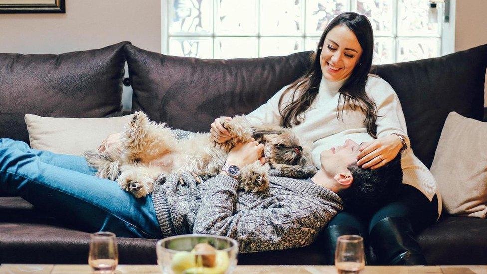 Pareja en un sofá con un perro.