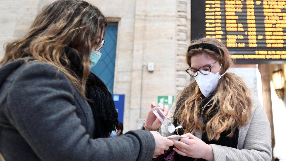 امرأتان ترتديان كمامتين وتعقّمان أيديهما في محطة للقطار في ميلان، 24 فبراير/شباط 2020