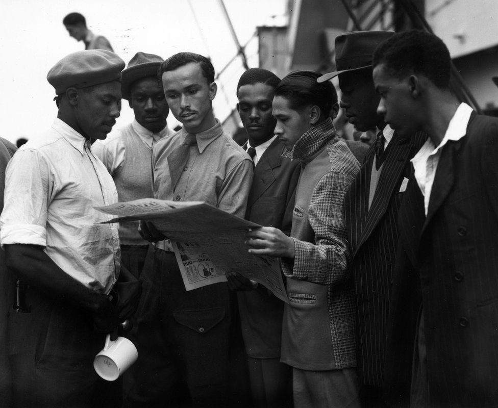 Immigrants on board the 'Empire Windrush' reading a newspaper