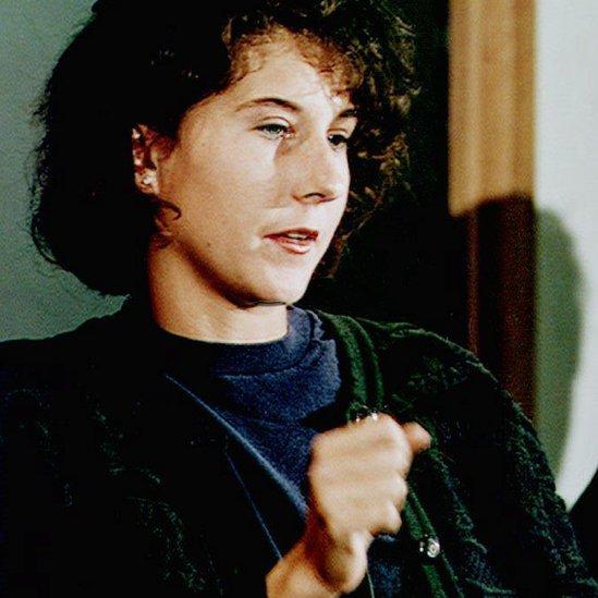 Seles hace el gesto con su mano del momento en el que fue apuñalada durante su primera comparecencia después del ataque en mayo de 1993.