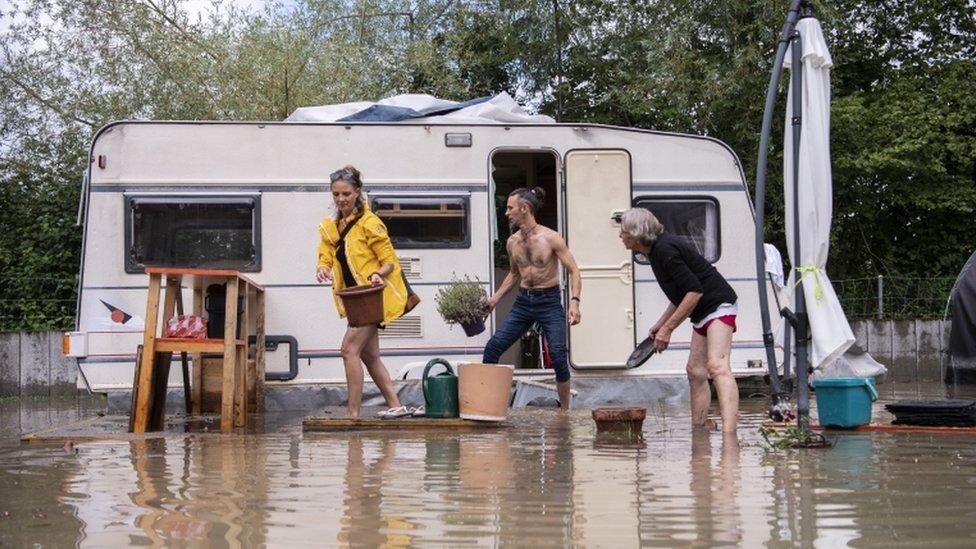 Personas intentan recuperar sus pertenencias en caravana en un camping inundado en Ottenbach, Suiza.