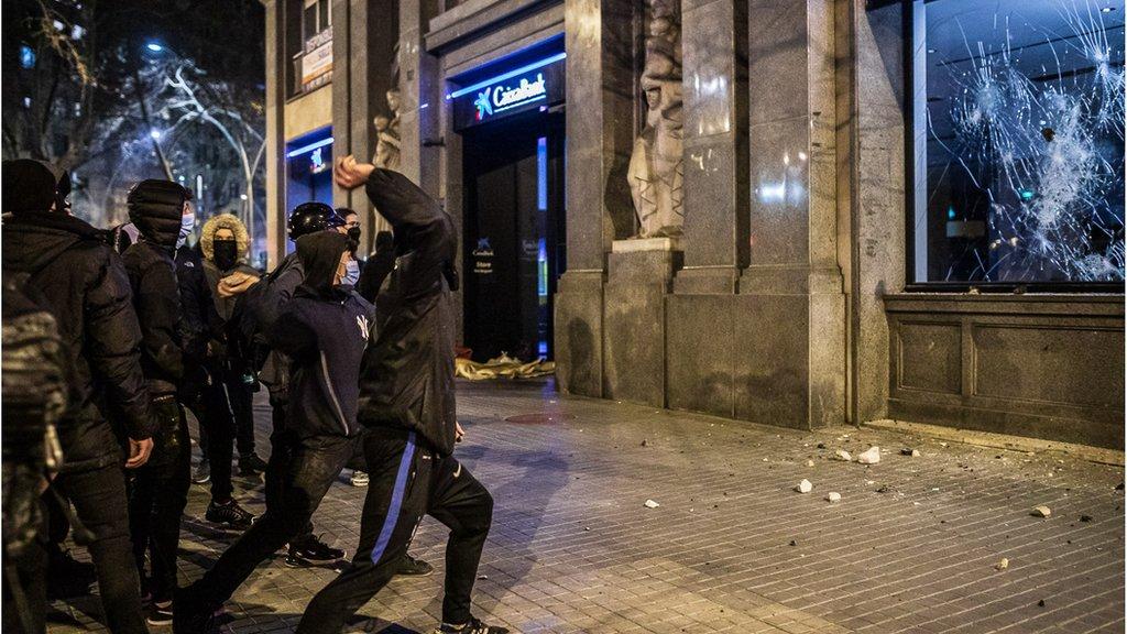 Unos manifestantes lanzan piedras contra una sucursal bancaria.