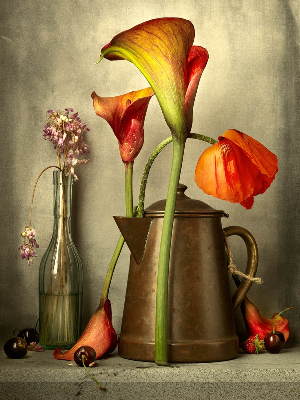 A bottle and a metal jug containing flowers, surrounded by cherries
