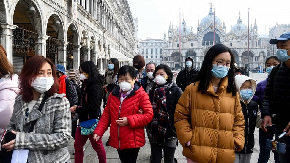 Tourists wearing protective facemasks visit the Piazza San Marco, in Venice, on February 24, 2020
