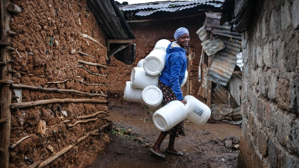 A woman is seen carrying her water Jerrycans past the corridors in Kibera Slums.