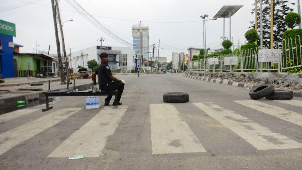 Seorang polisi memblokir jalan masuk ke kota Lagos, yang menerapkan karantina wilayah selama dua pekan.