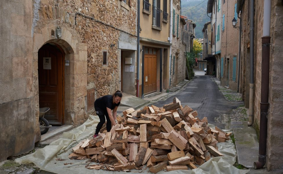A woman and a pile of wood in a street in Alet-les-Bains