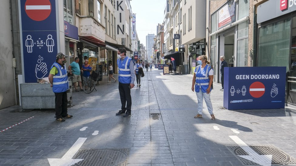 Stewards wearing face masks enforce a one-way system for pedestrians in Ostend, Belgium (21 May 2020)