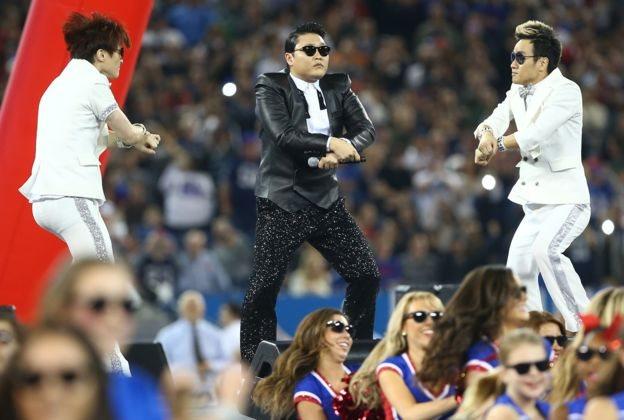 Співак Psy виконує рухи танцю Gangnam Style на сцені з двома танцюристами