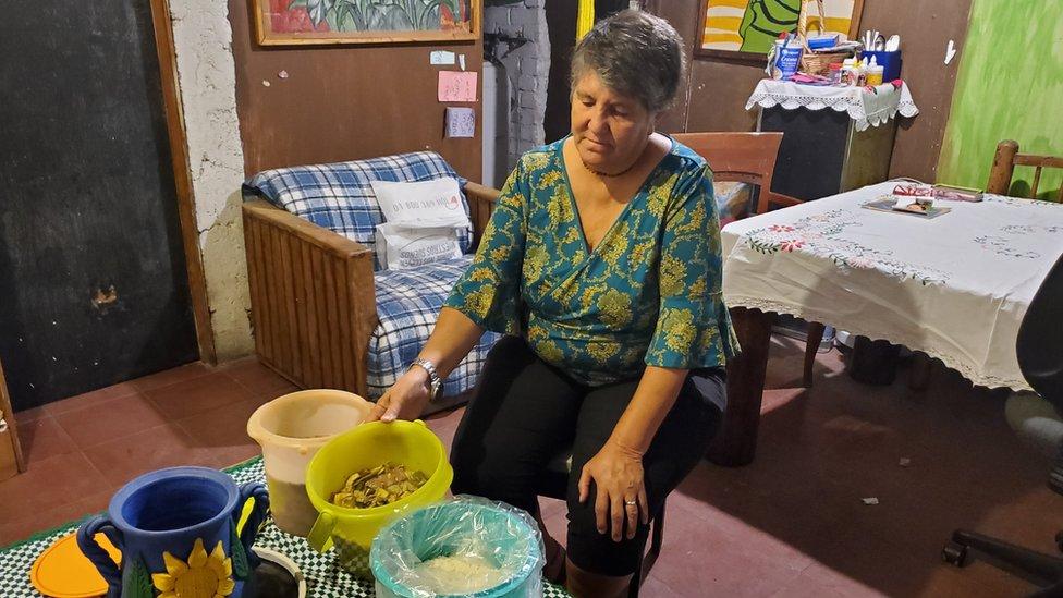 Margarita muestra los cubos de comida que recibe de las autoridades.