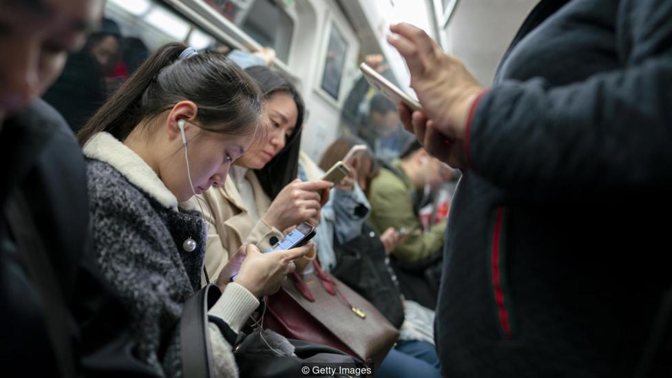 Personas en China miran su celular