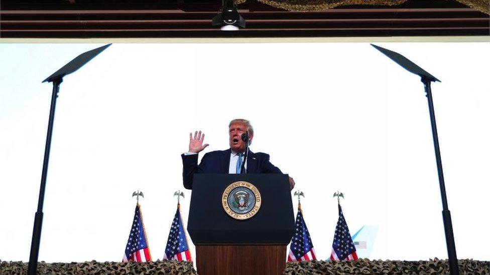 Дональд Трамп выступает с речью на фоне флагов США
