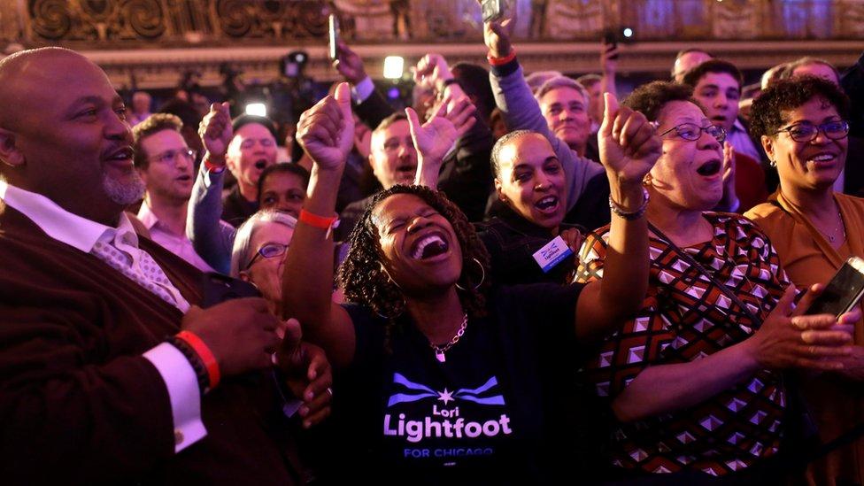 A woman celebrates Lori Lightfoot's victory
