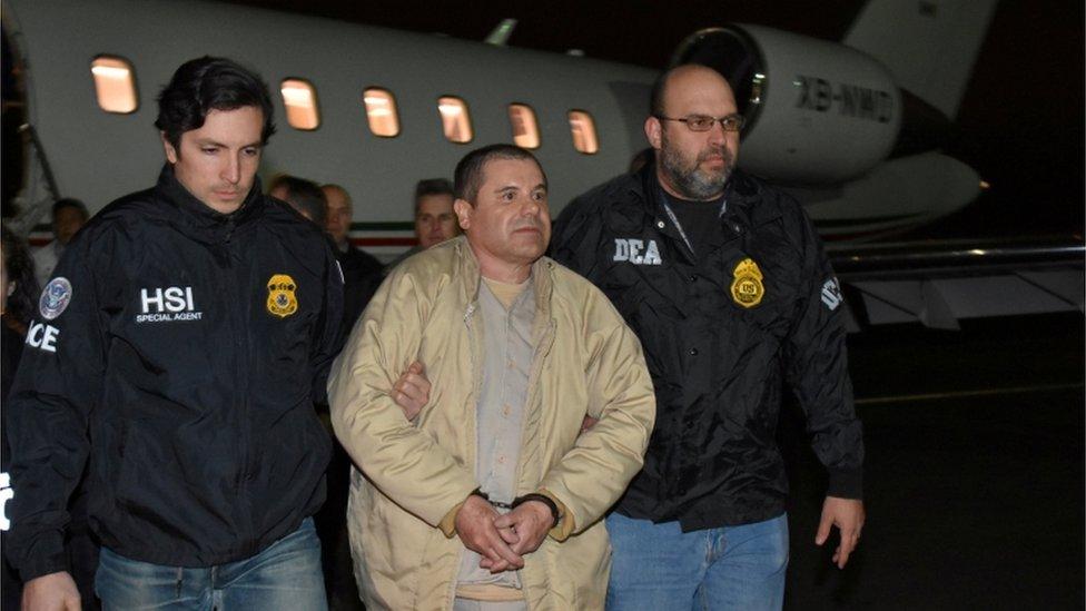 """""""El Chapo"""" esposado y escoltado por oficiales de la DEA."""