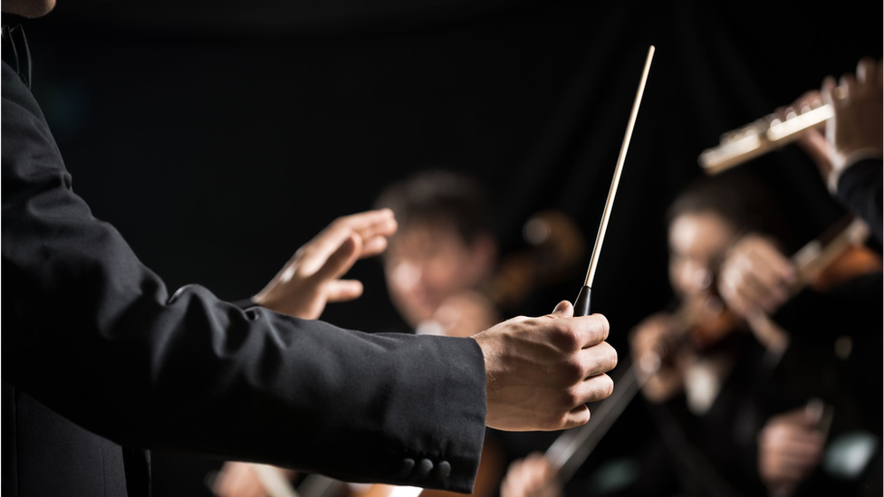 A maestro conducting an orchestra