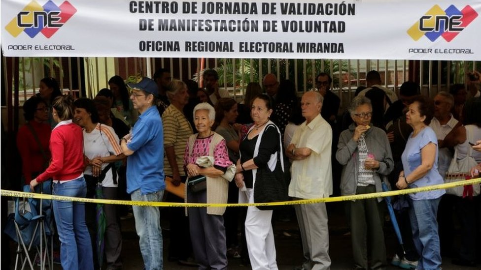 People stand in line outside a school during Venezuela's National Electoral Council (CNE) second phase of verifying signatures for a recall referendum against President Nicolas Maduro in Caracas, Venezuela June 20, 2016.