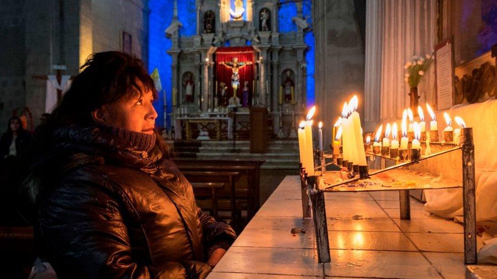 Mujer reza en catedral en Perú