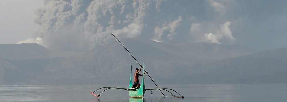 Small boat on Lake Taal with Taal volcano erupting behind