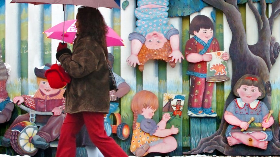 People are seen walking by the smiling faces and idyllic scenes of the Network Childcare Services