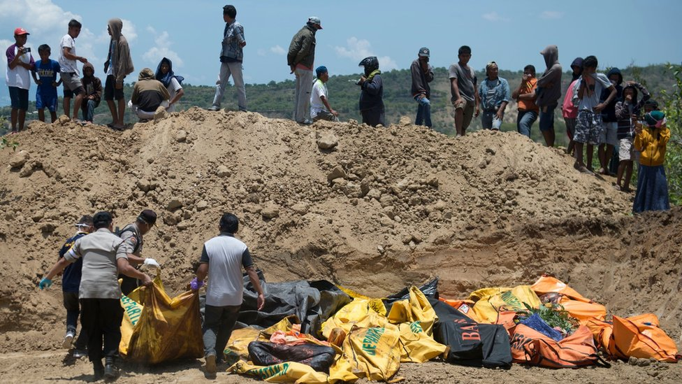 People carry body bags into a mass grave in Palu, Indonesia. Photo: 1 October 2018