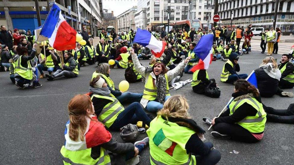Mujeres vestidas con un chaleco amarillo organizan una protesta en Francia.