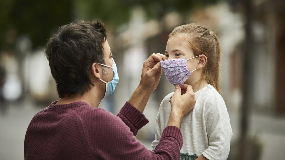 Hombre ajustándole la mascarilla a una niña