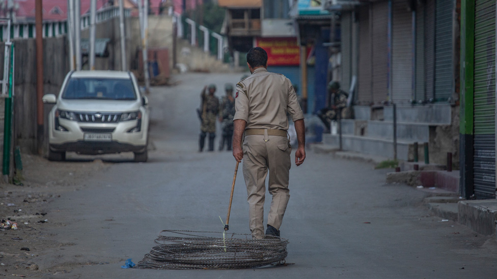A security officer drags a coil of barbed wire behind him