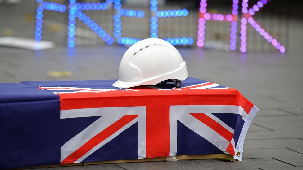 倫敦一場聲援香港集會上擺放蓋上舊英屬香港旗幟與白色安全帽的假棺材(12/12/2020)