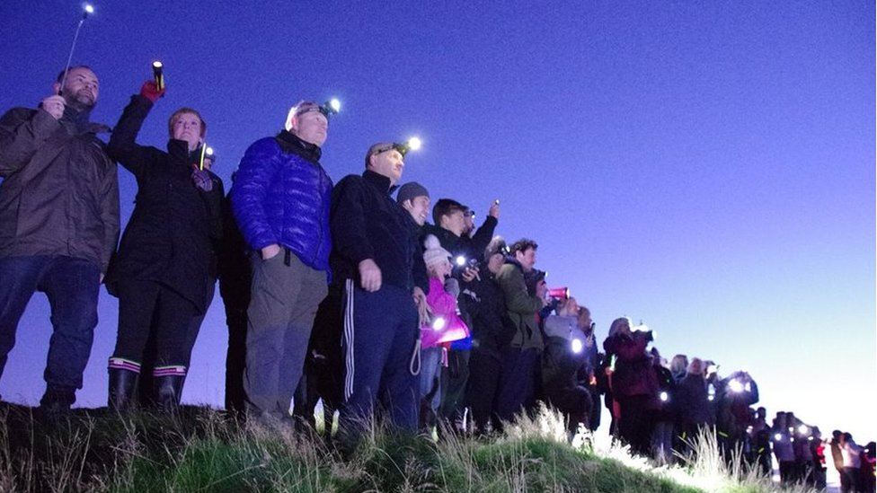 People hold torches atop Eston Nab