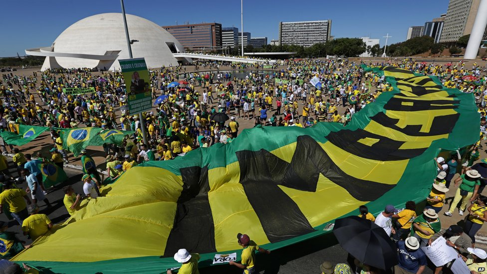 """Marchers carrying banners that read in Portuguese """"Dilma Out"""" and """"Impeachment Now,"""" in Brasilia, Brazil on 16 August 2015"""