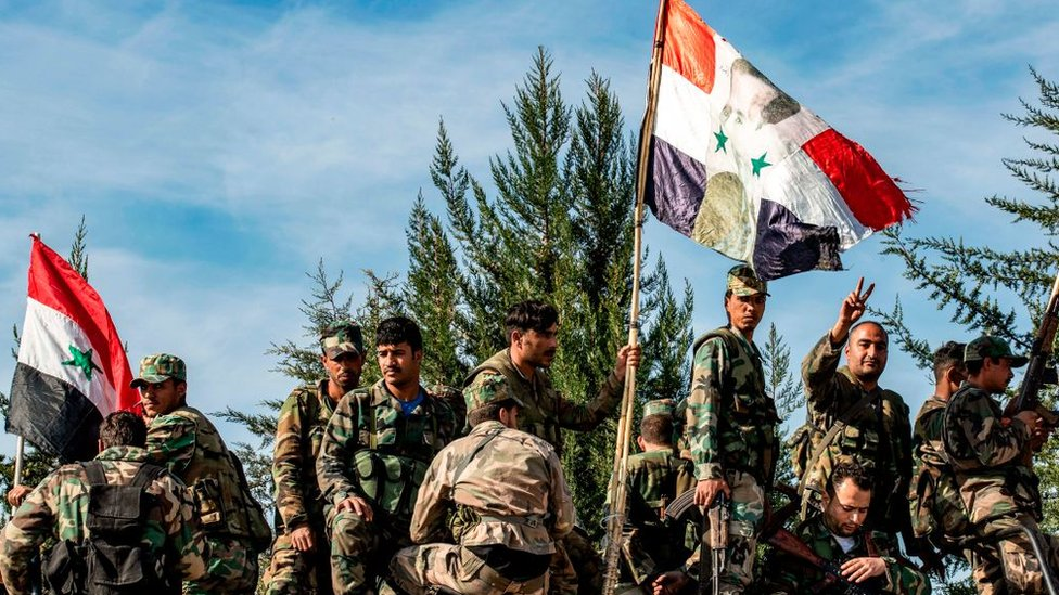 Soldados de las fuerzas gubernamentales posan en Siria con la bandera del país y la foto del presidente sirio Bashar al-Assad.