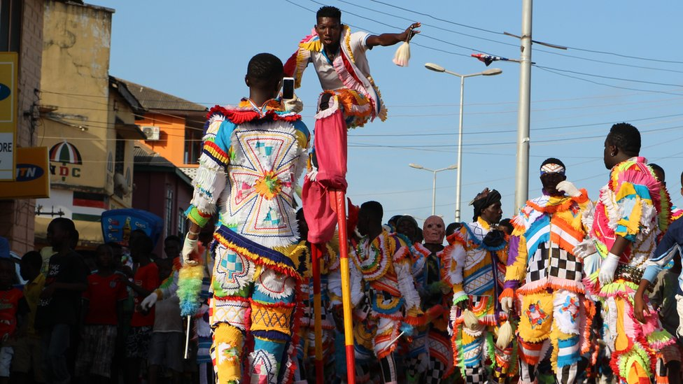 Man on stilts towers over other people on the parade in Sekondi Ghana
