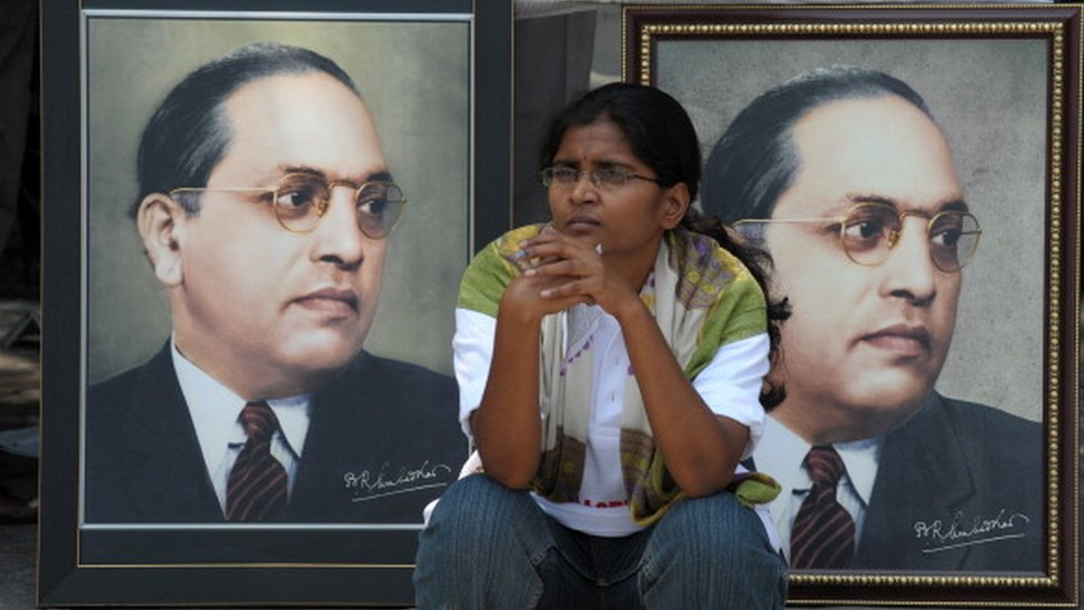 n Indian woman sits infront of portraits of Bhimrao Ramji Ambedkar during 122nd birth anniversary celebrations for Ambedkar in Hyderabad on April 14, 2012.