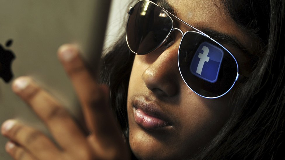 Indian girl with Facebook logo in sunglasses
