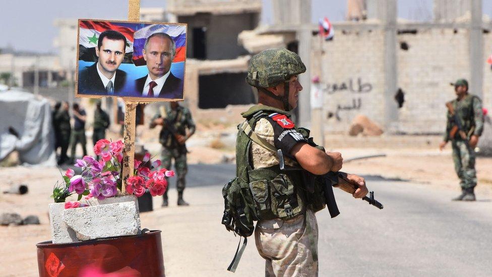 Putinova i Asadova slika na transparentu iza naoružanog vojnika