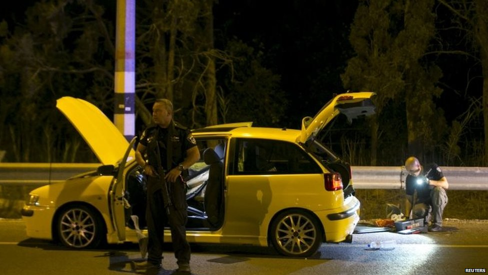An Israeli policeman next to the car used by an Israeli Arab to attack and injure four Israelis in Gan Shmuel near Hadera 11/10/2015