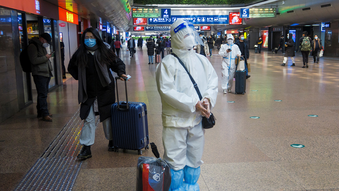 在北京火車站,有旅客身穿防護服,避免感染。