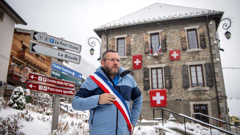 Nicolas Rubin, the Mayor of Châtel, poses with a scarf in the colours of France in front of the Town Hall
