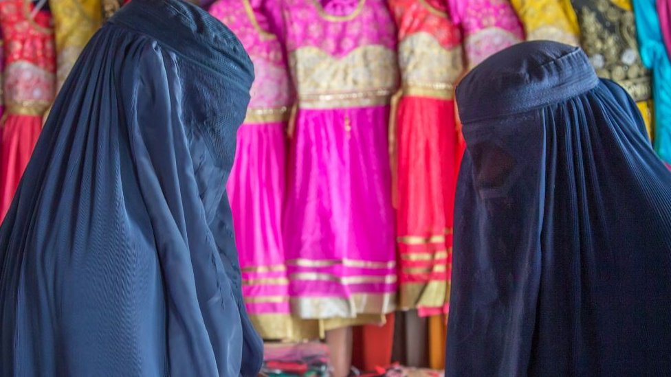 Women wearing burkas and buying clothes in Badakhshan province