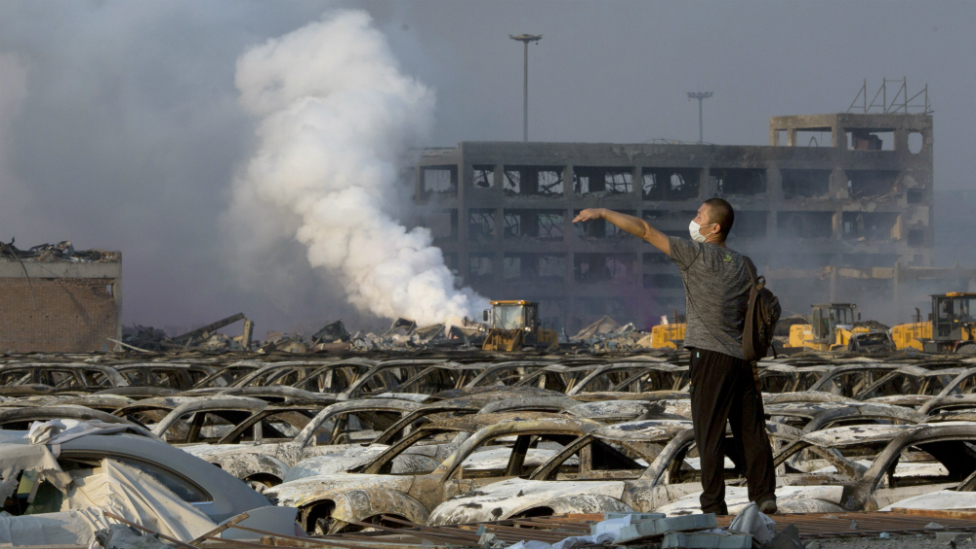 """A man walks through the site of an explosion at a warehouse in northeastern China""""s Tianjin municipality - 13 August 2015"""