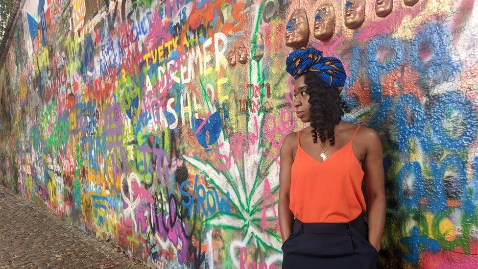 Liz Ogbonna-Godfrey stands next to a mural in Prague, Czech Republic.