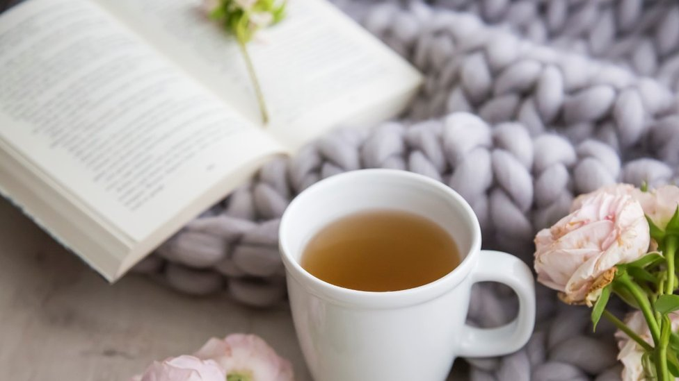 Una taza con una infusión y un libro