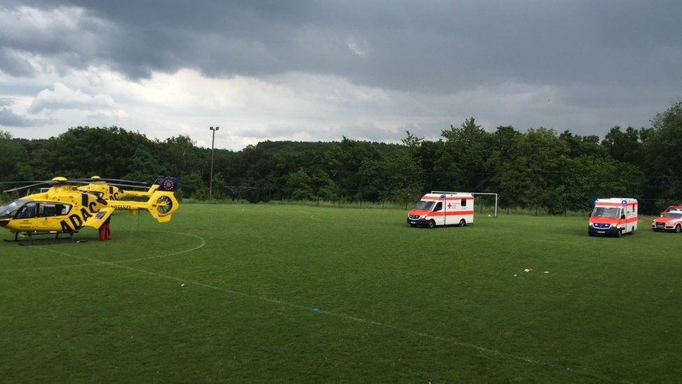 Photo provided by police shows helicopter, two ambulances and further emergency vehicles on football pitch, with dark grey skies (28 May 2016)